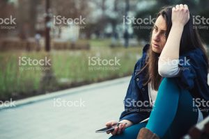 Sad-Woman-On-Curb-With-Cellphone