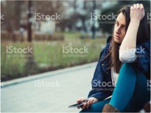 Sad-woman-sitting-on-curb